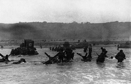 Some of the first assault troops to hit the beachhead hide behind enemy beach obstacles to fire on the Germans, others follow the first tanks plunging through water towards the Normandy shore on June 6, 1944.