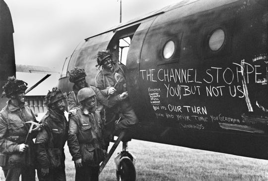 British paratroopers, their faces painted with camouflage paint, read slogans chalked on the side of a glider after Allied forces stormed the Normandy beaches during D-Day on June 6, 1944.