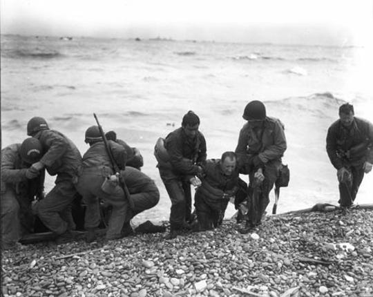 Members of a landing party help injured US soldiers to safety on Utah Beach during the Allied Invasion of Europe, on D-Day in Normandy, France, on June 6, 1944.
