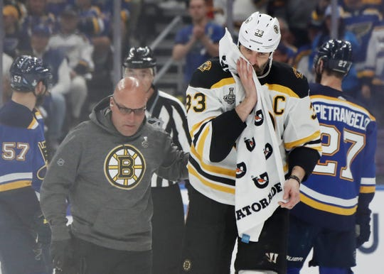Bruins defenseman Zdeno Chara is attended to after being hit in the face by a puck.