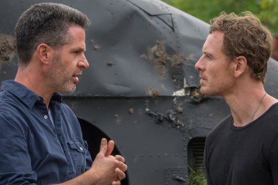 "Director Simon Kinberg (left) works on a scene with Michael Fassbender on the set of ""Dark Phoenix."""