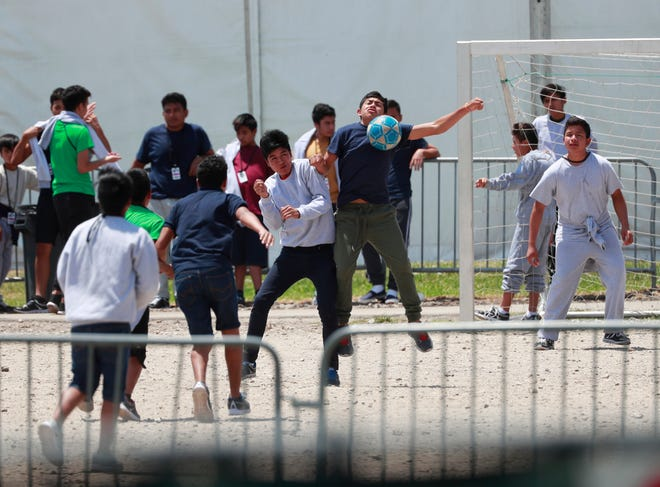 Migrant children play soccer at the Homestead Temporary Shelter for Unaccompanied Children on Good Friday in Homestead, Florida. The government has stopped reimbursing some contracted shelters for the cost of teaching immigrant children English-language courses and providing legal services and recreational activities.