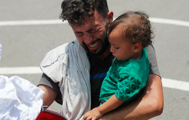 A man begs and prays not to be taken away by Mexican immigration authorities as he holds his child, during a raid on a migrant caravan that had earlier crossed the Mexico - Guatemala border, near Metapa, Chiapas state, Mexico, Wednesday, June 5, 2019.