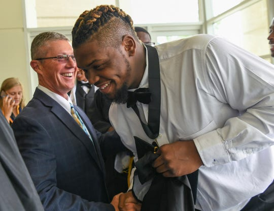 Graduate Zachh Pickens, right, greets T.L. Hanna High School football coach Jeff Herron before graduation in Bon Secours Wellness Arena in Greenville Thursday, June 6, 2019.