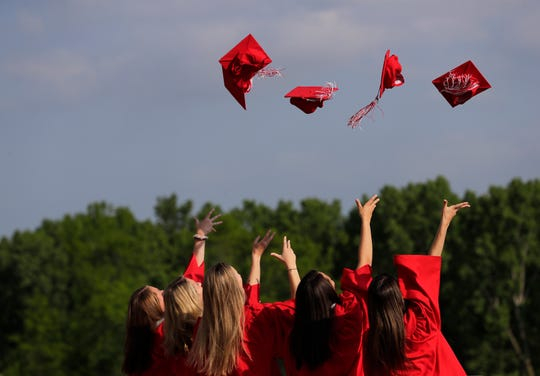 Students toss their caps into the air while taking pictures prior to the Kimberly High School commencement ceremony Wednesday in Kimberly. Post-graduation celebrations have become a traditional across Wisconsin.