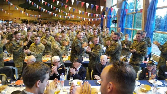 D-Day veterans get a standing ovation from U.S. military members at a banquet in Carentan, France.