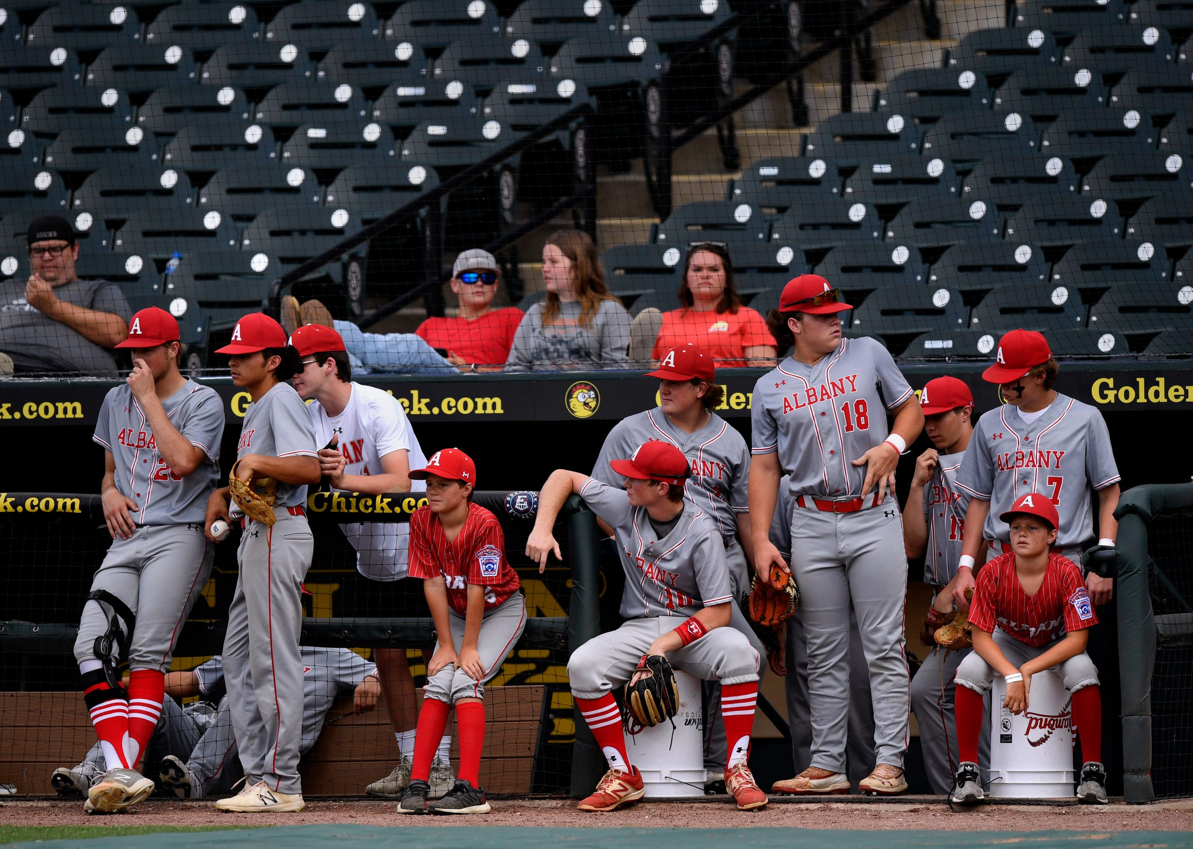Members of the Albany baseball team wait in the dugout for the start of their Class 2A semifinal game against Big Sandy. The Lions made it to state for the second time in three years.
