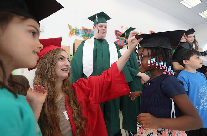 Class of 2019 graduate Kassidy Spearin adjusts kindergartener Olive Baiden's cap as she and fellow graduates prepare for an assembly at Cougar Valley Elementary School in Seabeck on Thursday. It's a yearly tradition for seniors who attended the elementary to return to provide advice to grade-schoolers.