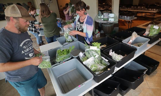 Erin and Roni Smith of Kitsap Fresh sort fresh veggies into bins as they pack up boxes for delivery and pickup at Run Dog Run Doggy Day Care in Kingston on Wednesday. A new warehouse in Kingston will mean the Smiths no longer have to borrow space to assemble orders.