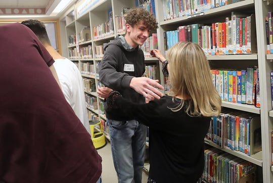 Aiden Cooper hugs his former kindergarten teacher, Lisa Williams, while he and fellow graduates visit Cougar Valley Elementary School in Seabeck on Thursday.