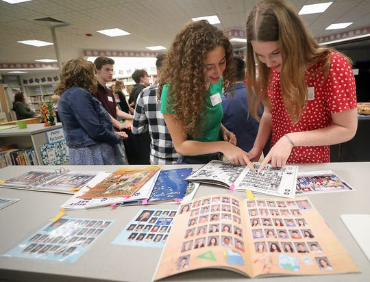 Central Kitsap Class of 2019's Nicquole Walsh and Emma Hibbs look through old yearbooks in the library while visiting Cougar Valley Elementary School on Thursday.