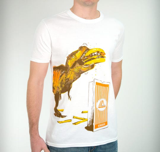 """Whataburger graphic tees include the T-REX Tee, Shark Attack Tee, Call of the """"W"""" Tee and the Hunger Attack Tee. The t-shirts are available for $19.99 on Whataburger's website."""