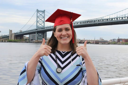 Brooke Trigiani gives a thumbs up near the Ben Franklin Bridge. The Moorestown native recently graduated with a degree in nursing from Rutgers University‒Camden after years of being a patient herself.