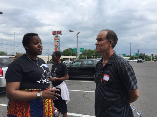 Ronsha Dickerson, a Camden resident, talks to Kevin Quinn of the New Jersey Economic Development Authority after taking him on a bus tour of the city.