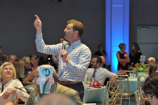 FOX19 Now Sports Director Joe Danneman engages guests in live auction.