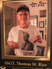 101st Airborne Division veteran Tom Rice holding a photo from his days in the service during WWII.