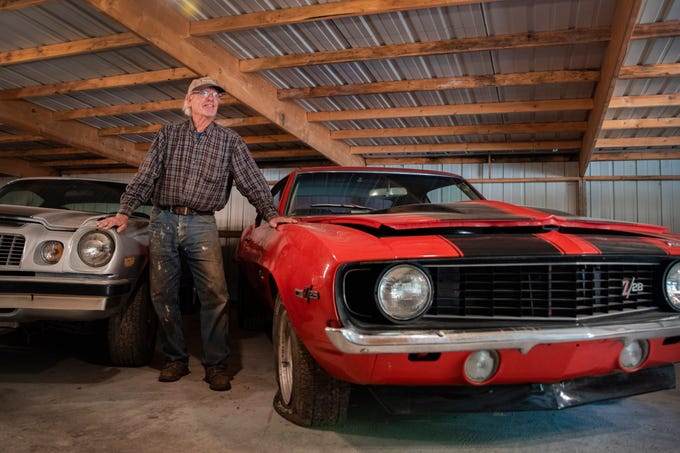 Coyote Johnson, 65, poses in one of five sheds where he keeps his vintage car collection. Johnson, of Red Oak, started collecting cars at age 16, and is auctioning most of them this fall.