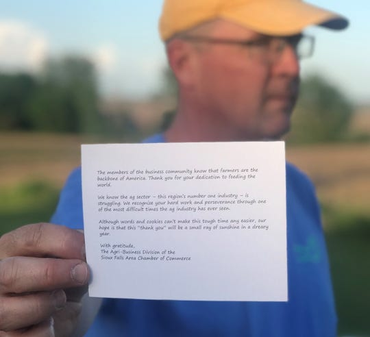 Ray of sunshine: Scott Lee with a note of appreciation delivered to his waterlogged Iowa farm -- with a bag of cookies -- by a representative of the Sioux Falls Area Chamber of Commerce.