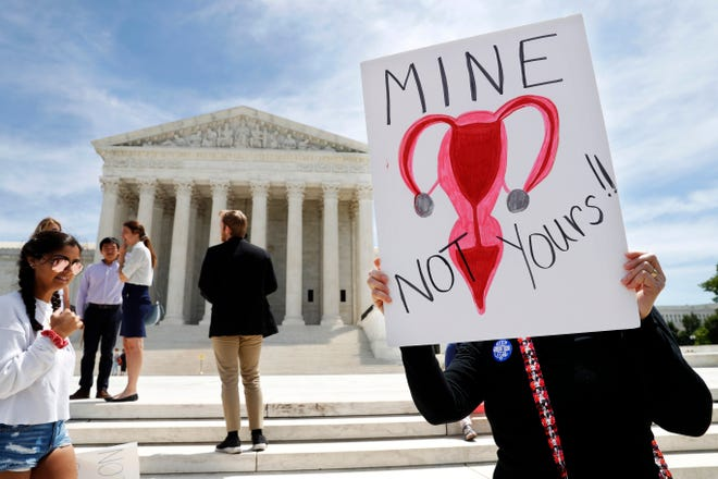 """Laurie Ploch, of Alexandria, Va., holds a sign with a drawing of a uterus on it that says """"mine not yours"""" as she protests against abortion bans on May 21 outside the Supreme Court in Washington."""