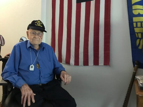 John McCurdy sits next to the American flag and Seabees flag that hang in his room at University Park Nursing and Rehabilitation. The World War II veteran has been a member of Carpenters Local 106 for 80 years.