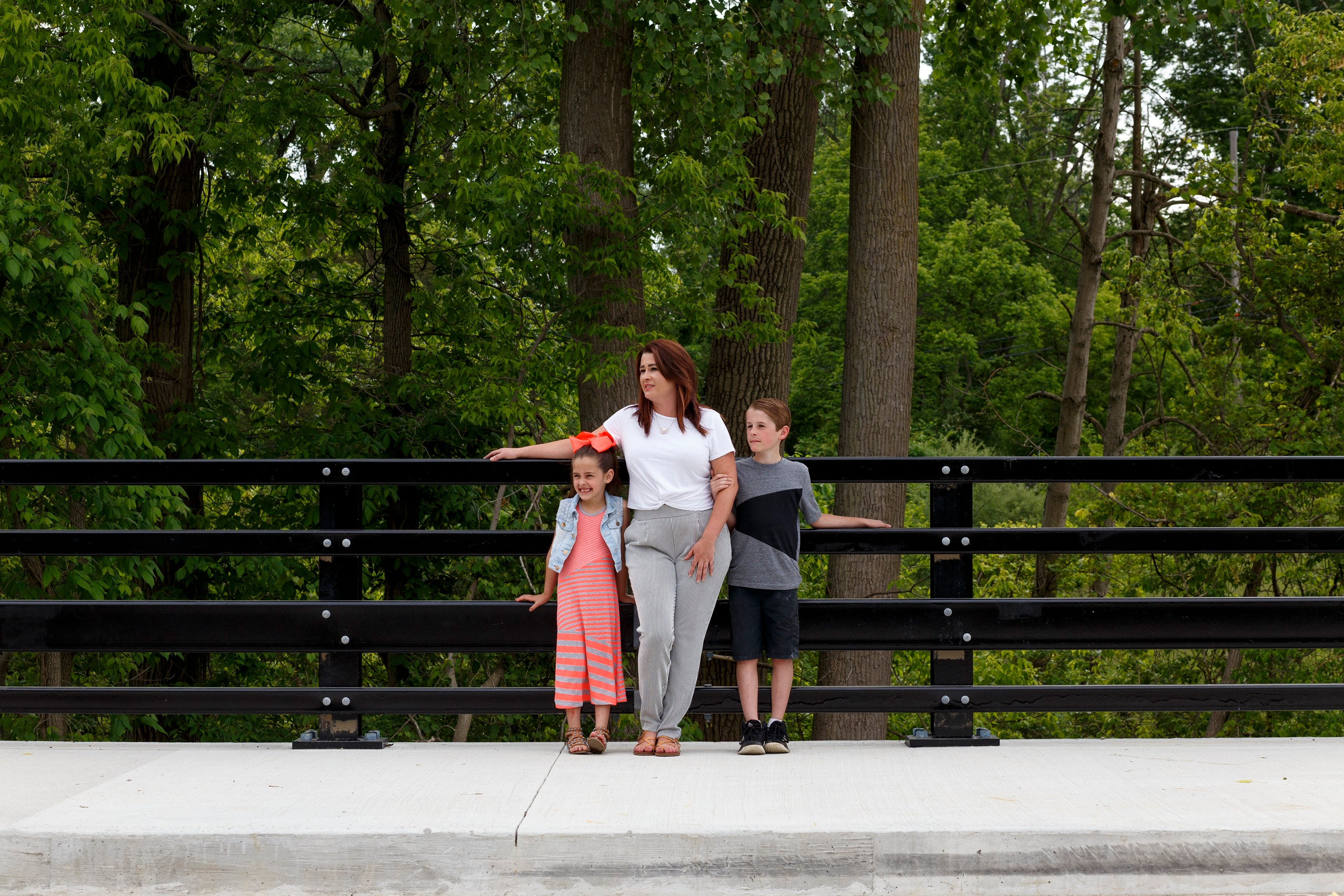 From left, Gracyn Miles, 6, Amanda Miles, 35, and Colin Miles, 9, look at traffic passing by on Tuesday in New Boston on the newly opened bridge.