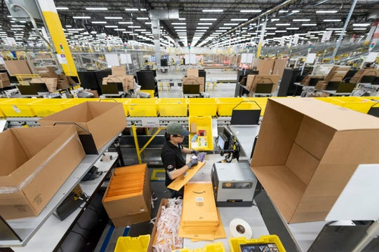 Fulfillment center associate Mike Lee works at a packing station for small items at the Amazon fulfillment center in Romulus.