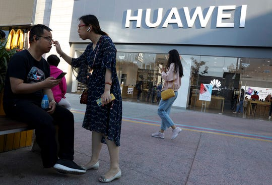 In this May 20, 2019, photo, people pass outside a Huawei store in Beijing. China could maximize harm on the U.S. economy not just by slashing flows of rare-earth materials, but by curbing supplies of small, powerful magnets that use them.