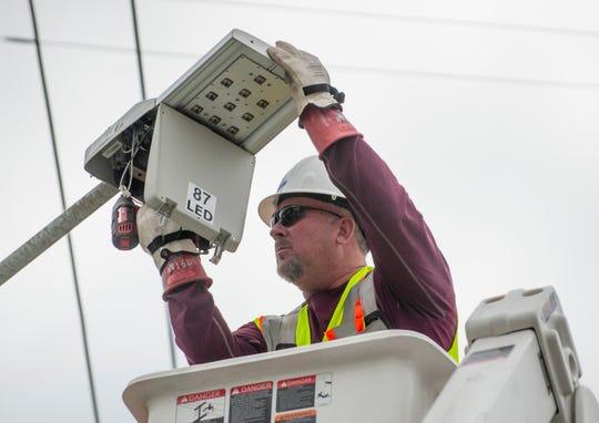 Lineman Allen Begley removes a burned out Leotek LED light panel before installing a new Cree brand LED light on Thursday.