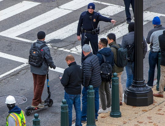 In this Dec. 5, 2018, photo, a police officer directs a rider on a Skip brand electric scooter to move off the street on Capitol Hill in Washington. As electric scooters have rolled into more than 100 cities worldwide, many of the people riding them have ended up in the emergency room with serious injuries. Others have been killed.