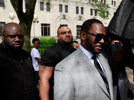 Musician R. Kelly, right, departs the Leighton Criminal Court building after pleading not guilty to 11 additional sex-related charges, Thursday, June 6, 2019, in Chicago.