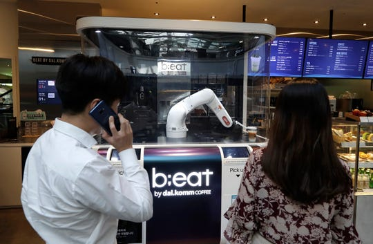 Customers wait for coffees in front of a robot named b;eat after placing an order at a cafe in Seoul, South Korea.