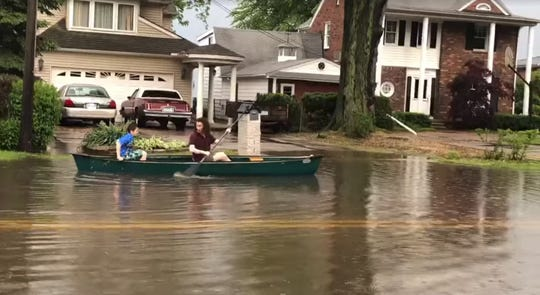 People row a canoe down Jefferson Ave. in St. Clair Shores between 11 Mile and 12 Mile.