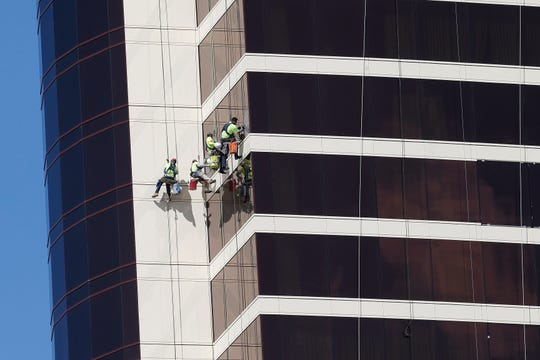 Window washers work on Encore Boston Harbor in Everett, Mass.