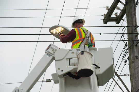Lineman Allen Begley installs a new Cree brand LED light on Remington Street near Dequindre in a north-side Detroit neighborhood on Thursday.