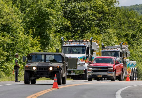Military police direct traffic along Route 293 near the site where an armored personnel vehicle overturned killing at least one person, Thursday, June 6, 2019, in Cornwall, N.Y.