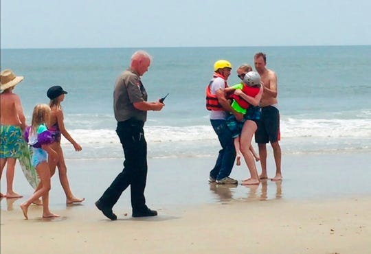 In this photo provided by Oak Island Water Rescue members of the Oak Island Water Rescue return a rescued child who was on a unicorn raft, hundreds of yards off the beach in Oak Island, N.C., Monday, June 3, 2019.