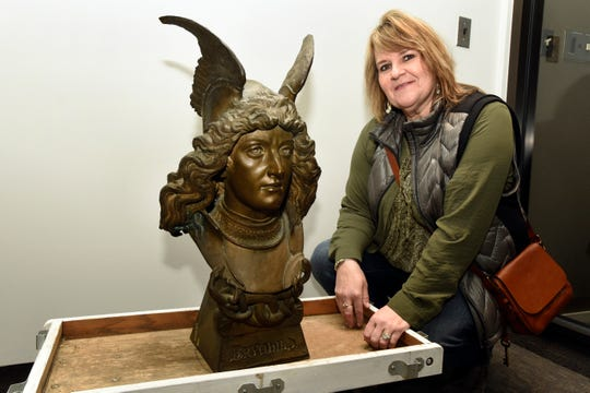 Roberta Petty-Woods of Sterling Heights shows off a bust of Brunhild,  during the Trash or Treasure event.