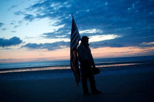 Udo Hartung from Frankfurt, Germany, a World War II reenactor, holds the U.S. flag as he stands at dawn on Omaha Beach, in Normandy, France, Thursday.