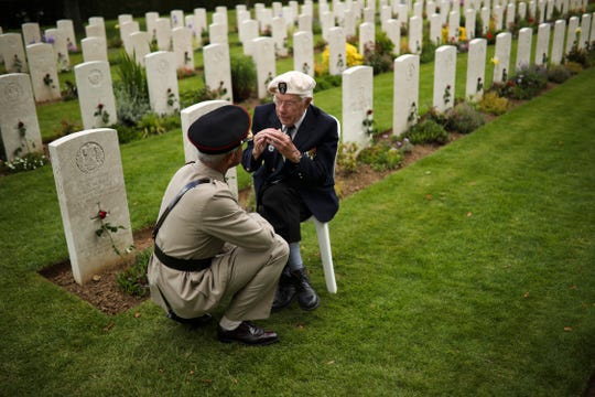 A World War II veteran talks to a soldier at the end of a ceremony to mark the 75th anniversary of D-Day at the Bayeux War Cemetery in Bayeux, Normandy, France, Thursday.