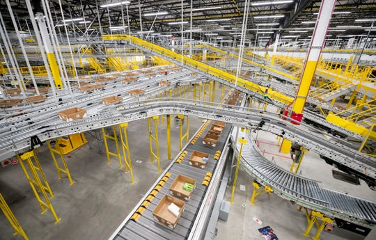 Thousands of packages move on conveyor belts through the Amazon fulfillment center in Romulus.