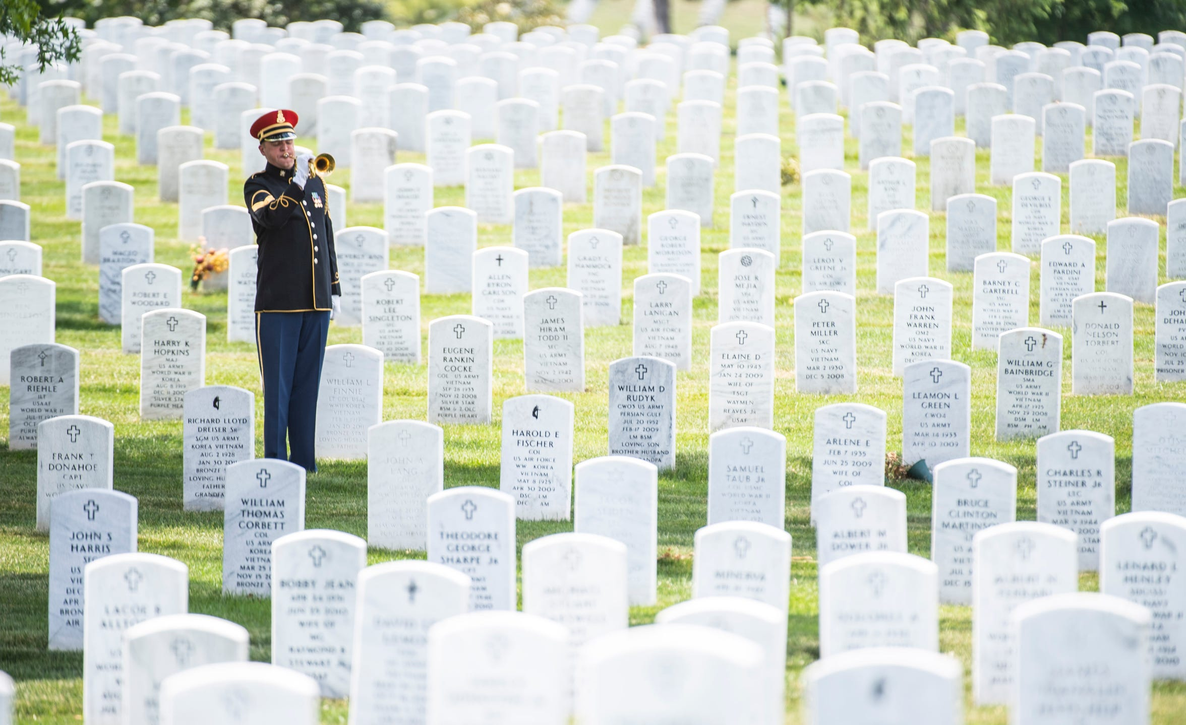 "A solo trumpet player honors U.S. Army World War II veteran Carl Mann of Evansville, Ind., with ""Taps"" as he is buried at Arlington National Cemetery on June 6, 2019 in Arlington, VA."