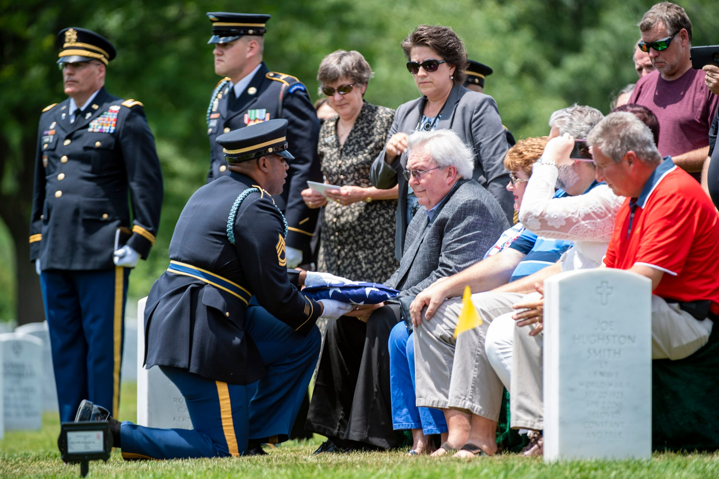 Carl Man II is presented with the flag during U.S. Army World War II veteran Carl Mann of Evansville, Ind., burial at Arlington National Cemetery on June 6, 2019 in Arlington, VA. For his service in World War II, Mann was awarded three Purple Hearts and seven Bronze Stars.