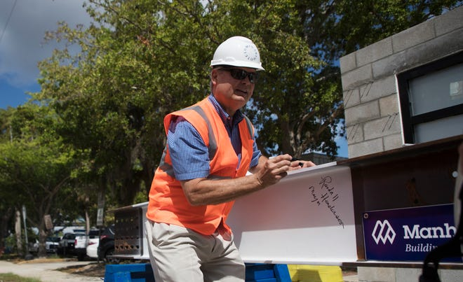 Fort Myers mayor Randy Henderson signs a steel beam during a topping ceremony at the Luminary Hotel in downtown Fort Myers on Thursday.
