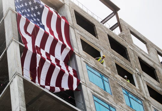 An  American flag is unveiled during    a topping off ceremony for the Luminary Hotel in downtown Fort Myers on Thursday.