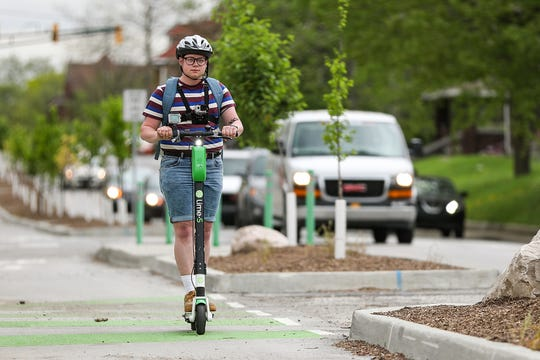"Lo Ray rides a Lime scooter on a one-and-a-half-mile commute from their job in the downtown area of Indianapolis on Wednesday, May 1, 2019. Ray does not own a car and often relies on the scooters to get to work, the grocery store or to meet with friends.  ""It's been really helpful to know that there's an additional way I can get around without needing a car,"" Ray said."