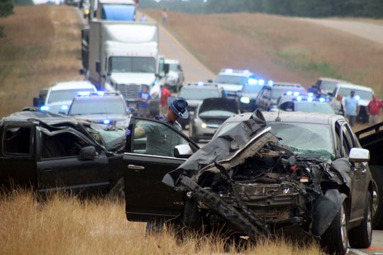 A Mississippi Highway Patrol state trooper investigates a wreck on U.S. Highway 45 south of Scooba in Kemper County, Miss., Wednesday, June 5, 2019. Three people were killed and several were injured Wednesday in a wreck involving multiple vehicles, including a school bus with no children aboard, on a rural Mississippi highway not far from the scene of another crash that killed eight people two days earlier.