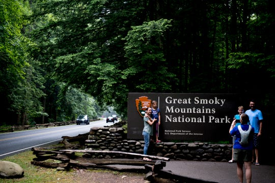 Visitors take a photo at the entrance to Great Smoky Mountains National Park in Gatlinburg, Tennessee on Wednesday, June 5, 2019.