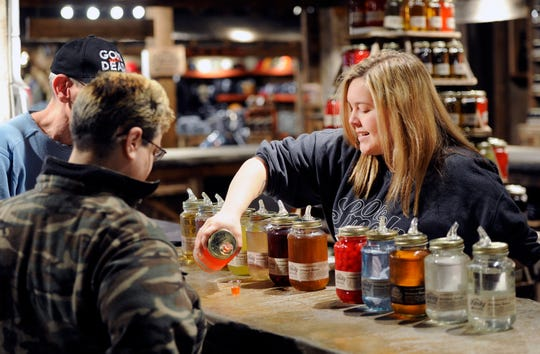 Brittany Ogle, right, pours moonshine samples for customers at Ole Smoky Moonshine in Gatlinburg on April 16, 2015.
