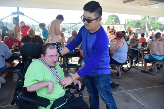 Justin Trout gets his baseball medallion from coach Isaac Lee at a baseball awards picnic held at Karns Pool Monday, June 3, 2019.