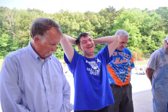 Knoxville Challenger Sports board Chairman Nic Arning, Chris Howard, and board member Glenn Valentine say a prayer before a baseball awards picnic held at Karns Pool Monday, June 3, 2019.
